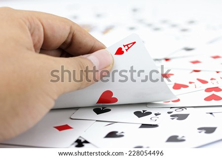 Closeup photos that focuses on the ace card of heart in the hand,on the background from the stack of cards - stock photo