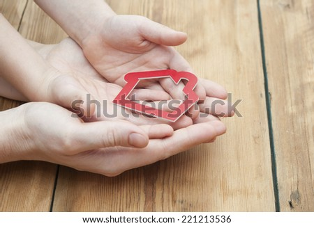 closeup picture hands of mom and child holding red house  - stock photo