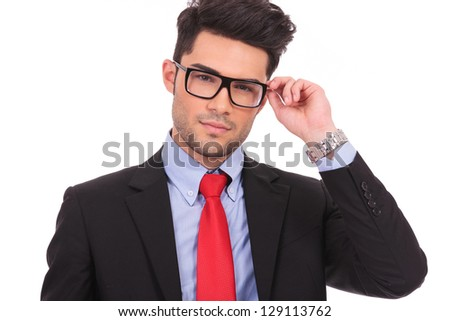 closeup picture of a young business man holding his eyeglasses and looking at the camera, on white background - stock photo