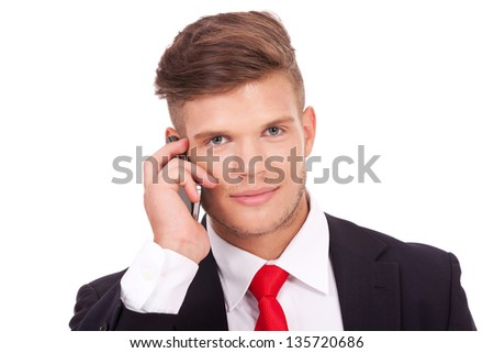 closeup picture of a young business man talking on the phone and smiling to the camera. isolated on white background