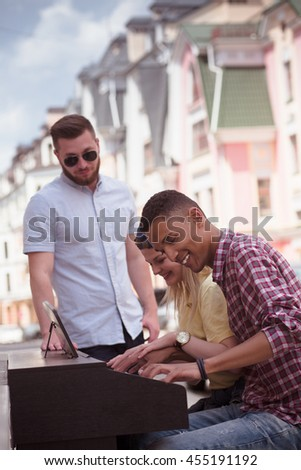 Closeup picture of afro-american man playing piano with his friend lady outdoors. People spending time all together in city center. Keyboard of piano concept. - stock photo