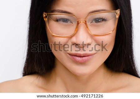 Closeup picture of beautiful Korean woman in glasses in studio. Happy Asian lady smiling for camera and promoting fashionable glasses.