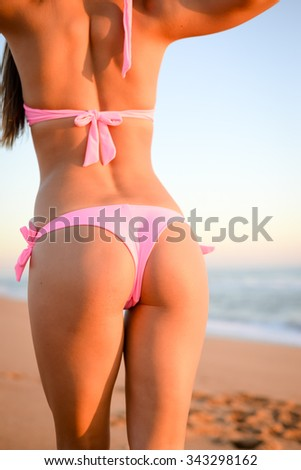 Closeup picture of beautiful young woman's body in bikini. Backview of sexy lady on summer beach blurred light sky background. - stock photo