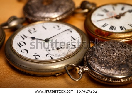 Closeup picture of different sizes pocket watches. Old paper background.  - stock photo