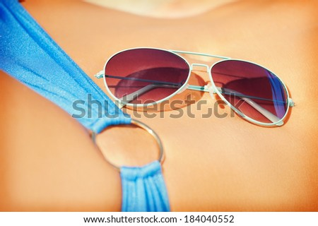 closeup picture of female belly, bikini and shades - stock photo