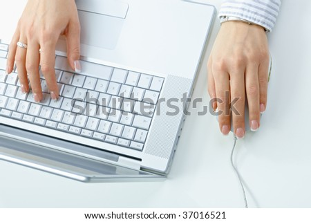 Closeup picture of female hand typing on computer keyboard, using mouse.