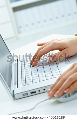 Closeup picture of female hands using laptop computer and mouse. - stock photo
