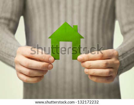 closeup picture of hands holding green house