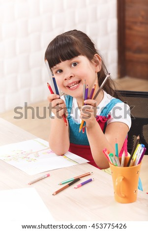 Closeup picture of little girl showing her multicoloured pencils while sitting at table and drawing pictures. - stock photo