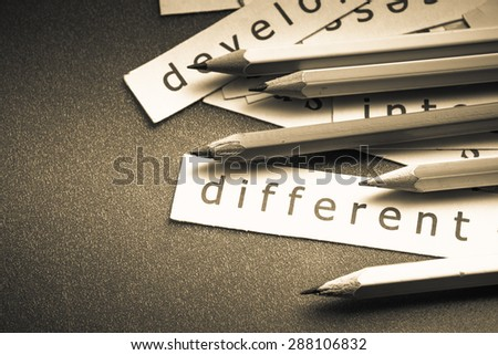 Closeup pieces of paper and pencil with Different word - stock photo