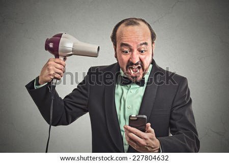 Closeup portrait angry business man screaming looking on smartphone holding hairdryer something blows his mind isolated grey background. Face expression emotion. Stressful life of corporate executive - stock photo