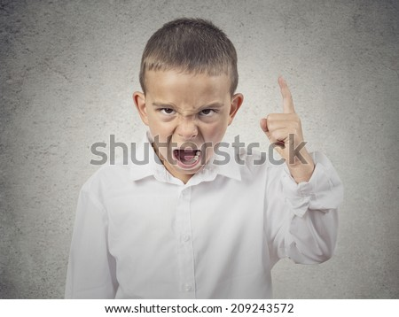 Closeup Portrait Angry child, Boy Screaming finger pointing up, demanding justice isolated grey wall background. Negative human Emotions, Facial Expressions, body language, attitude, perception