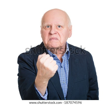 Closeup portrait, angry cranky upset senior mature man, worker, business putting up fist about to give you knuckle sandwich, isolated white background. Negative human emotion facial expression feeling
