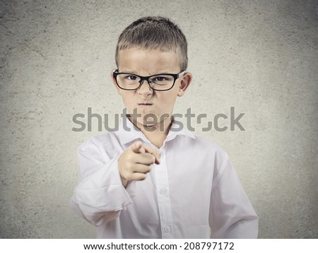 Closeup portrait angry, mad child disguised as boss, executive businessman, pointing finger at someone, displeased, isolated grey background. Human face expressions, emotions, feelings, body language - stock photo