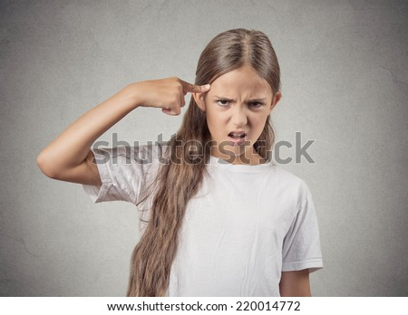 Closeup portrait angry mad teenager girl gesturing with her finger against temple asking are you crazy? Isolated grey wall background. Negative human emotions facial expression feeling body language - stock photo