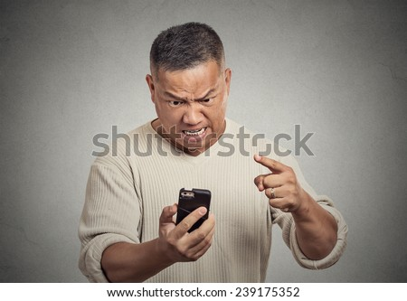 Closeup portrait angry middle aged man, guy, mad worker, pissed off employee while on mobile, pointing with finger at his smart phone isolated grey wall background. Negative emotion facial expression - stock photo