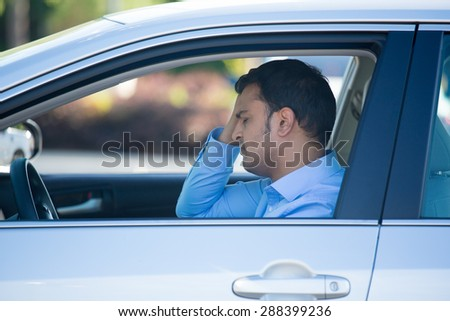 Closeup portrait, angry young sitting man pissed off by drivers in front of him, hand on head, isolated city street background. Road rage traffic jam concept - stock photo