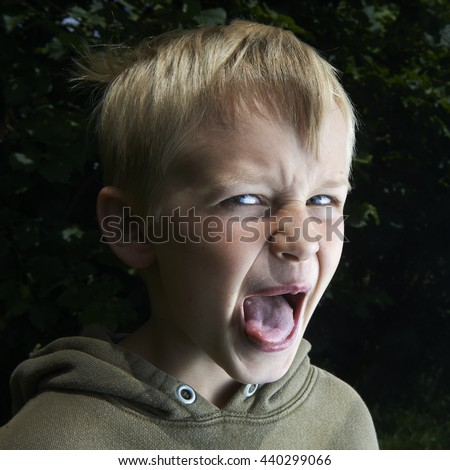 Closeup portrait angry young Unhappy boy. Negative human emotions, Boy shows his tongue, facial expressions, Body Language, attitude - stock photo