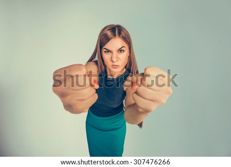 Closeup portrait angry young woman showing fists about to punch hit someone or to have nervous atomic breakdown isolated black background. Negative human emotions facial expression feelings attitude - stock photo
