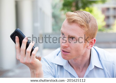 Closeup portrait, annoyed young man, pissed off by what he heard or saw on his cell phone, isolated outdoors background - stock photo