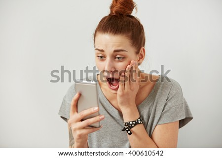Closeup portrait anxious or shocked young freelancer woman looking at phone seeing bad news or photos with disgusting emotion on her face isolated grey background. Human emotion, reaction, expression. - stock photo