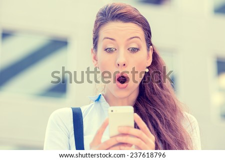 Closeup portrait anxious young girl looking at phone seeing bad news or photos with disgusting emotion on her face isolated outside city background. Human emotion, reaction, expression  - stock photo