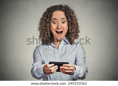 Closeup portrait anxious young girl looking at phone seeing bad news or photos with wow shock emotion on her face isolated grey wall background. Human reaction, expression. Breaking news concept  - stock photo