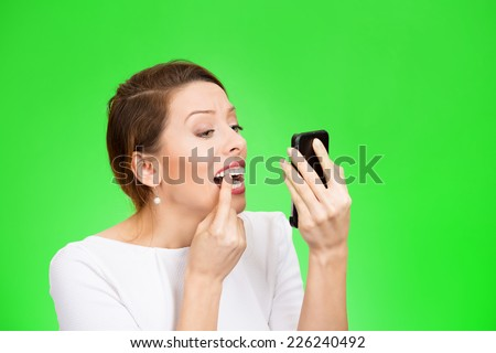Closeup portrait attractive young woman looking in a mirror checking her teeth isolated on green background  - stock photo