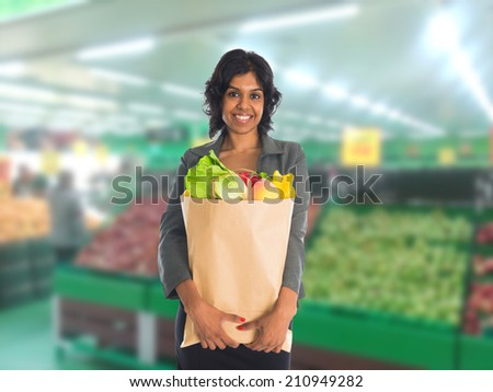 Closeup portrait, beautiful, pretty young woman in sweater picking up, choosing green leafy vegetables in grocery store  - stock photo