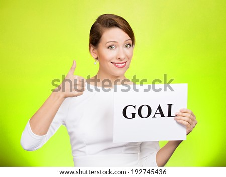 Closeup portrait beautiful smiling, happy business woman holding sign goal, giving thumbs up isolated green background. Positive emotions, facial expressions, reaction, attitude, determination  - stock photo