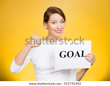 Closeup portrait beautiful smiling, happy business woman holding sign goal, giving thumbs up isolated yellow background. Positive emotions, facial expressions, reaction, attitude, determination  - stock photo