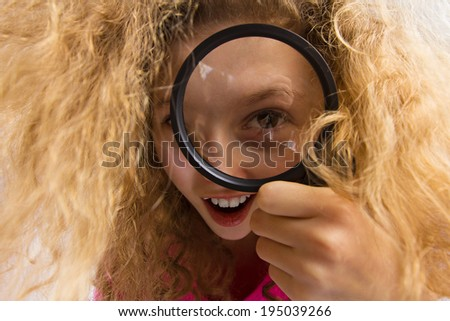 Closeup portrait beautiful, surprised little girl with curly blonde hair looking through magnifying glass. Human emotions, facial expressions, attitude, reaction, curiosity, life perception, childhood - stock photo