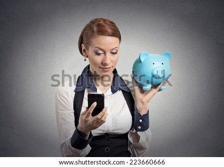 Closeup portrait business woman corporate employee holding piggy bank looking at smart phone isolated grey background. Financial savings, banking concept, customer deal contract agreement satisfaction - stock photo