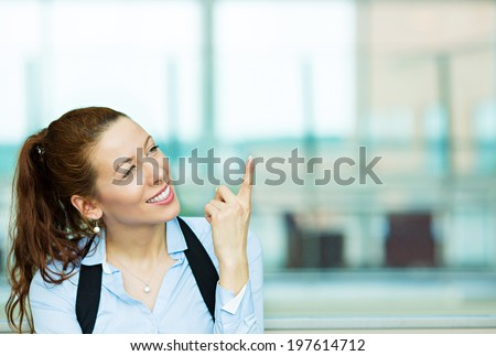 Closeup portrait charming smiling joyful happy business woman looking upwards daydreaming something thinking pointing finger up isolated background corporate building office. Emotion facial expression - stock photo