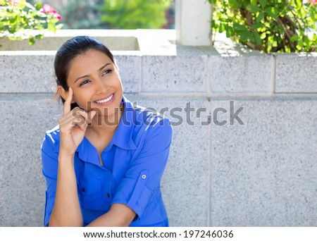 Closeup portrait, charming upbeat smiling joyful happy young woman looking upwards daydreaming something nice, isolated outdoors gray background. Positive human emotions facial expressions feelings - stock photo