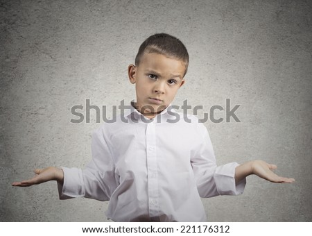 Closeup portrait clueless, unhappy child boy with arms out asking what's problem who cares, so what, I don't know isolated grey wall background. Negative human emotion facial expression body language  - stock photo