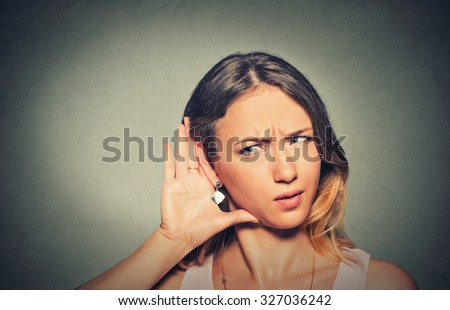 Closeup portrait concerned young nosy woman hand to ear gesture carefully intently secretly listening juicy gossip conversation news isolated grey background. Human face expression. Privacy violation - stock photo