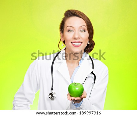 Closeup portrait, confident happy health care professional, doctor, nurse in lab coat, offering you fruit, isolated green background. Apple a day keeps doctor away concept. Nutrition, healthy diet - stock photo