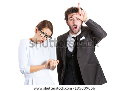 Closeup portrait couple, business people. Bully husband, man standing upfront, angry, giving bully sign with hand, shy, timid wife, nerdy woman with glasses, isolated white background. Human emotions - stock photo