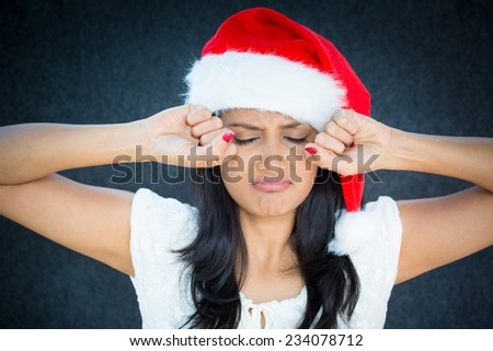 Closeup portrait, cute christmas woman in red santa claus hat, white dress, putting hands up to face about to cry, isolated gray black background. Negative emotion facial expressions - stock photo
