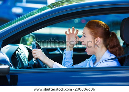 Closeup portrait displeased angry pissed off aggressive woman driving car, shouting at someone, hands up in air isolated traffic background. Emotional intelligence concept. Negative human expression - stock photo