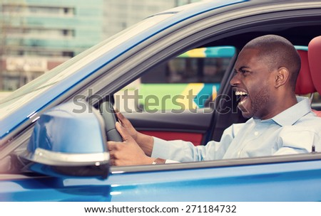 Closeup portrait displeased angry pissed off aggressive young man driving car shouting at someone isolated traffic background. Emotional intelligence concept. Negative human face expression - stock photo