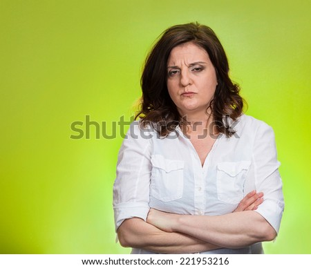 Closeup portrait displeased pissed off angry grumpy pessimistic woman with bad attitude, arms crossed looking at you, isolated green background. Negative human emotion facial expression feeling - stock photo