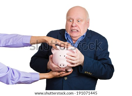 Closeup portrait elderly, shocked senior business man, grandfather, holding piggy bank, looking scared trying to protect his savings from being stolen isolated white background. Financial fraud, crime