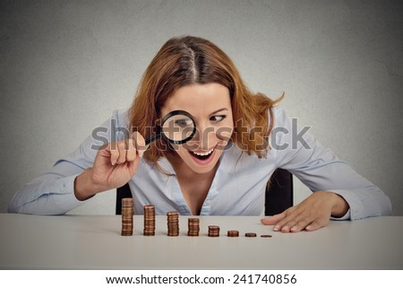 Closeup portrait excited greedy business woman wall street executive looking at growing stack of coins through magnifying glass isolated grey wall office background. Human face expression. Economy - stock photo