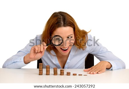 Closeup portrait excited greedy business woman wall street executive looking at growing stack of coins through magnifying glass isolated on white background. Face expression. Economy banking concept  - stock photo