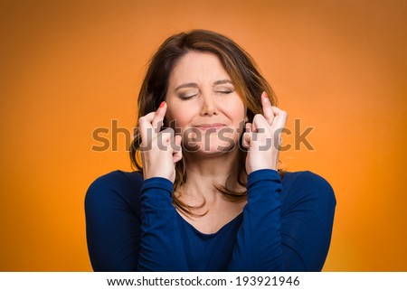 Closeup portrait excited, hopeful beautiful woman, mother crossing her fingers, eyes closed, hoping, asking best isolated orange background. Human face expression, emotions, feeling attitude reaction - stock photo