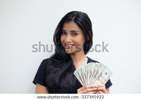Closeup portrait, excited successful young business woman in black shirt holding money dollar bills in hand isolated white wall background. Positive emotion facial expression feeling. Financial reward - stock photo