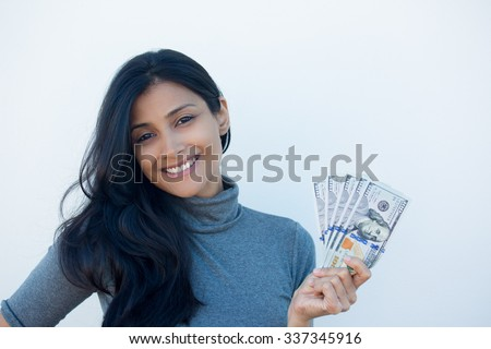 Closeup portrait, excited successful young business woman in gray shirt holding money dollar bills in hand, isolated white wall background. Positive emotion facial expression feeling. Financial reward - stock photo