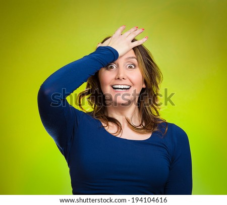 Closeup portrait excited young middle aged woman placing hand on head, palm on face gesture in duh moment, isolated green background. Human emotion facial expression feelings, body language, reaction - stock photo